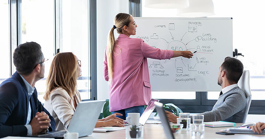 Business woman showing SEO strategies on whiteboard to team